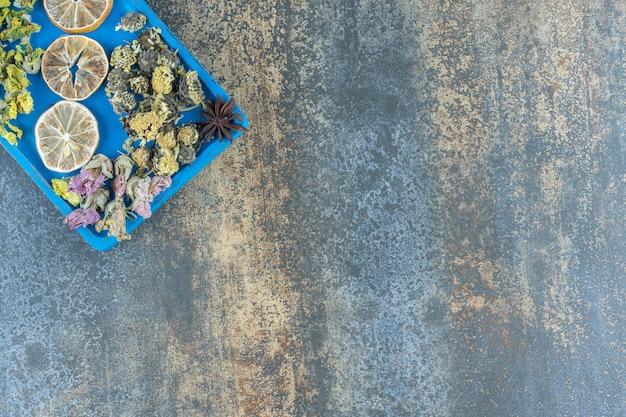 Gedroogde bloemen en plakjes citroen op blauw bord.