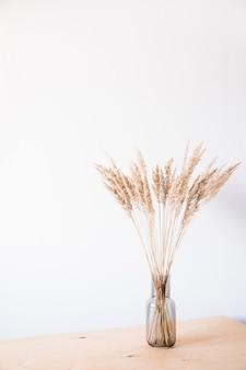Gedroogde bloemen in een glazen vaas met een lege lichte muur