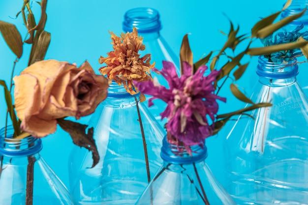 Gedroogde bloemen in plastic flessen als symbool van een uitstervend ecosysteem uit plastic potten