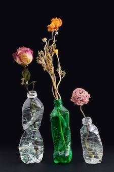 Gedroogde bloemen in verpletterde plastic flessen op een zwarte achtergrond