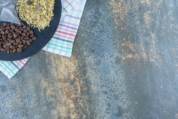Gedroogde bloemen, koffiebonen en theezakjes op zwart bord.