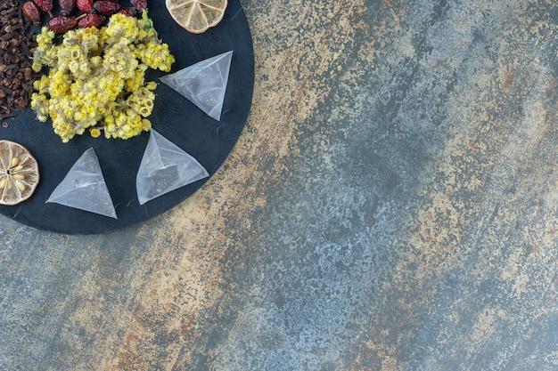 Gedroogde bloemen, kruidnagel, rozenbottels en theezakjes op zwart bord.