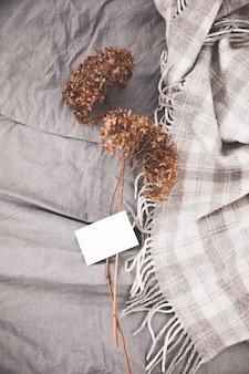 Gedroogde bloemen romantisch boeket en witte lege kaart stapel op bed.