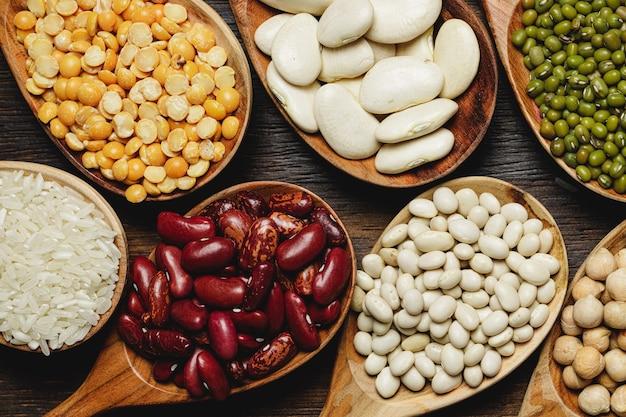 Gedroogde bonen in houten lepels op tafel, close-up