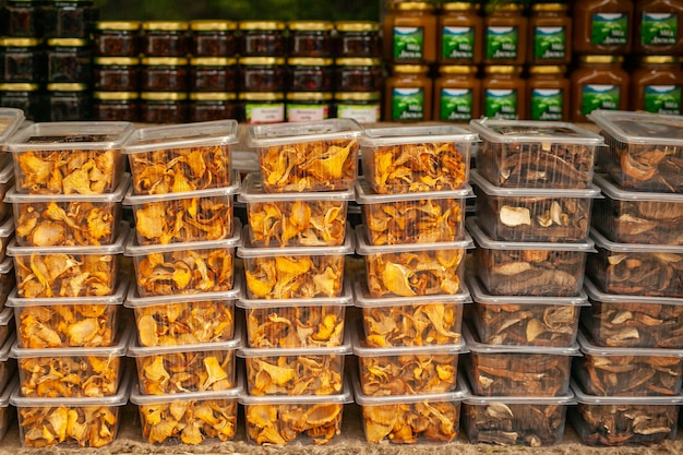 Gedroogde champignons in plastic containers op een landelijke kerstmarkt - cantharellen en eekhoorntjesbrood. bosbouw.