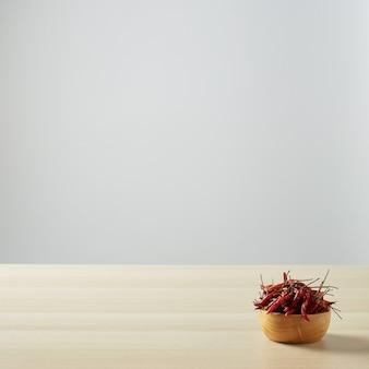 Gedroogde chilipepers in een houten kom op een houten tafel en witte muur voor kopieerruimte voor tekst