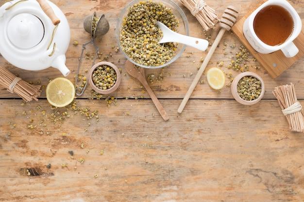 Gedroogde chinese chrysant bloemen; theepot; theezeefje; honing beer; container en verse citroenthee op houten tafel