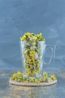 Gedroogde chrysant bloemen in glas op blauwe achtergrond.