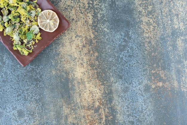 Gedroogde chrysant en citroenschijfjes op bruine plaat.