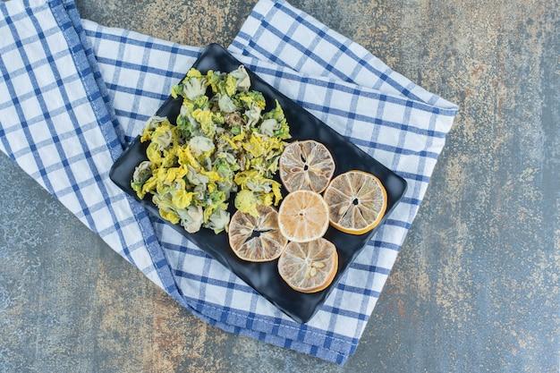 Gedroogde chrysant en citroenschijfjes op zwarte plaat.