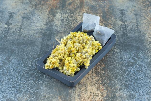 Gedroogde chrysant en theezakjes op donkere plaat.