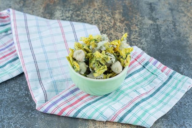 Gedroogde chrysantenbloemblaadjes in groene kom met tafelkleed.