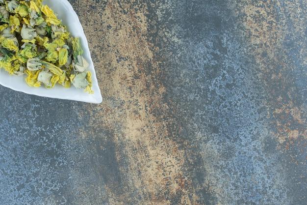 Gedroogde chrysantenbloemblaadjes op bladvormige plaat.