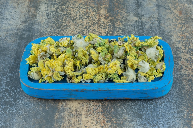 Gedroogde chrysantenbloemblaadjes op blauw bord.