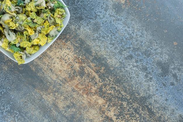 Gedroogde chrysantenbloemblaadjes op witte plaat.