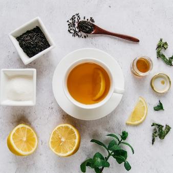 Gedroogde citroenthee met suiker; munt en honing op concrete achtergrond