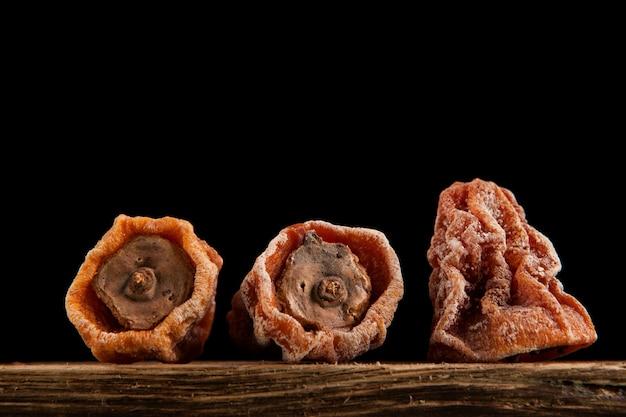 Gedroogde dadelpruim (hoshigaki). getextureerde gerimpelde vruchten op een donkere achtergrond.