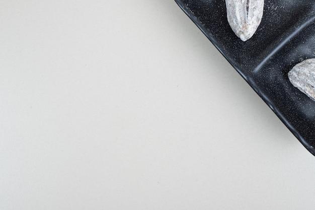 Gedroogde dadelpruimvruchten op zwarte plaat
