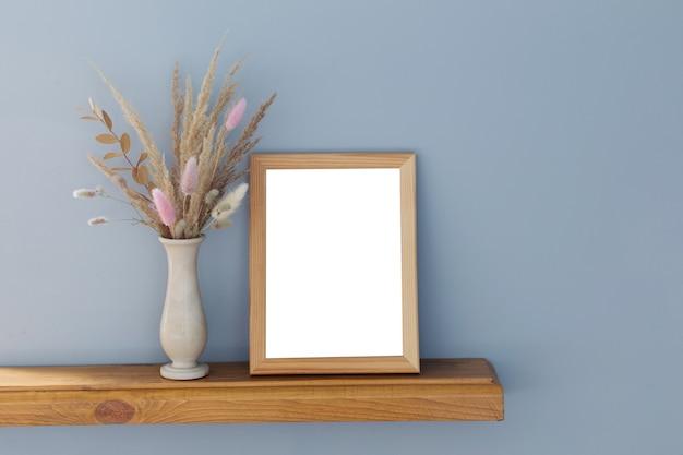 Gedroogde decoratieve granen in vaas met geïsoleerd wit frame op houten plank
