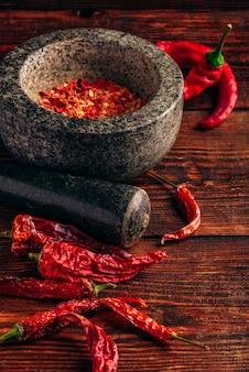 Gedroogde en geplette rode chilipeper in stenen vijzel