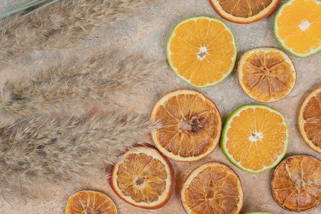 Gedroogde en verse stukjes sinaasappel op marmeren achtergrond.