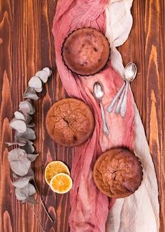 Gedroogde eucalyptus populus bladeren en citrus plakjes met drie gebakken cake en lepels op linnen kleding over de houten tafel