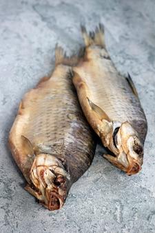 Gedroogde gedroogde gouden vis, riviervis, ligt op een grijze tafel