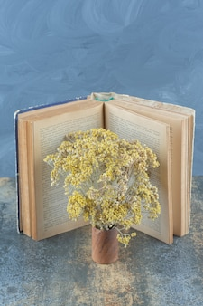Gedroogde gele bloemen en boek op marmer.