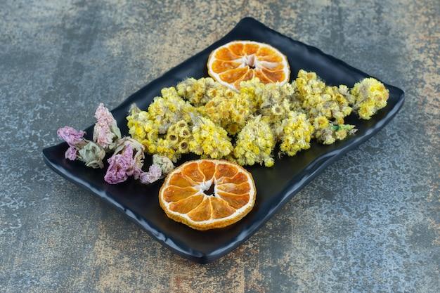 Gedroogde gele bloemen en sinaasappelschijfje op zwarte plaat.