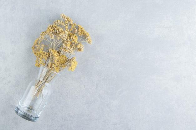 Gedroogde gele bloemen in glazen pot.