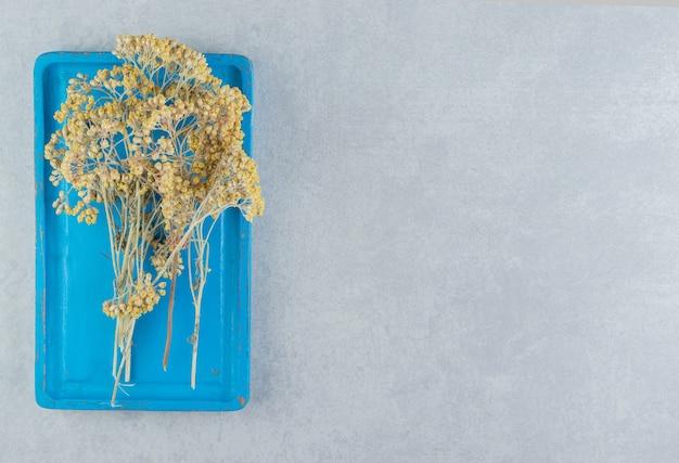 Gedroogde gele bloemen op blauw bord.
