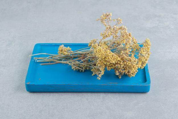 Gedroogde gele bloemen op blauw bord