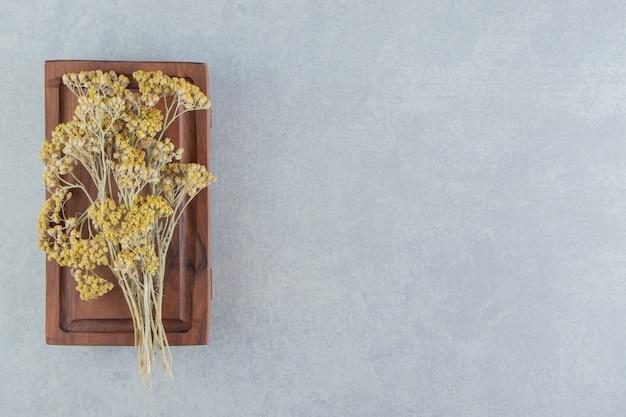 Gedroogde gele bloemen op een houten bord.