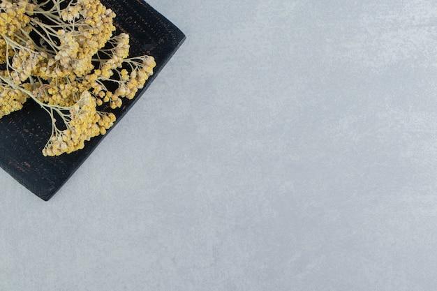 Gedroogde gele bloemen op zwart bord.