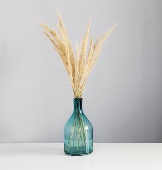 Gedroogde gele decoratieve granen in glazen vaas op witte tafel