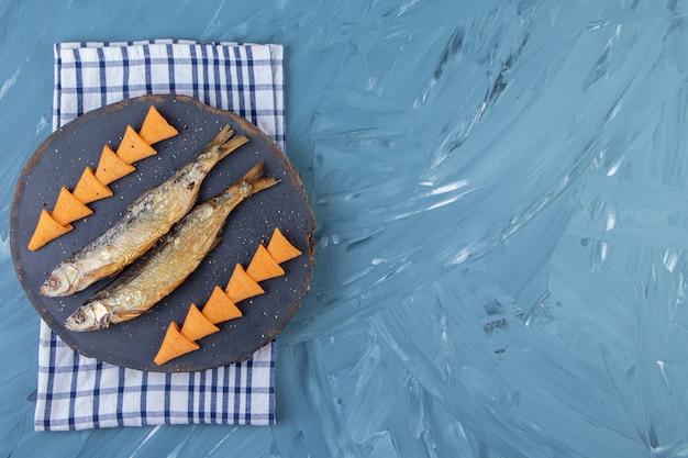 Gedroogde gezouten sprot en kegelchips op een bord op een handdoek, op de marmeren achtergrond.