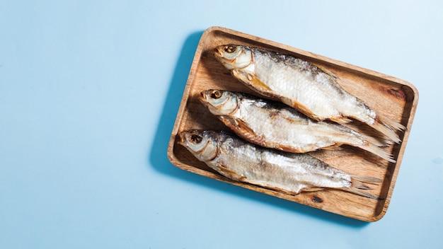 Gedroogde gezouten vis op een houten dienblad.