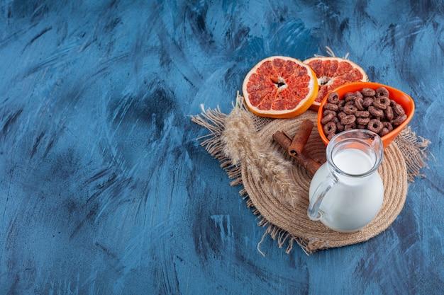 Gedroogde grapefruit, een kom met maïsringen en een kan melk op een handdoek, op de blauwe tafel.