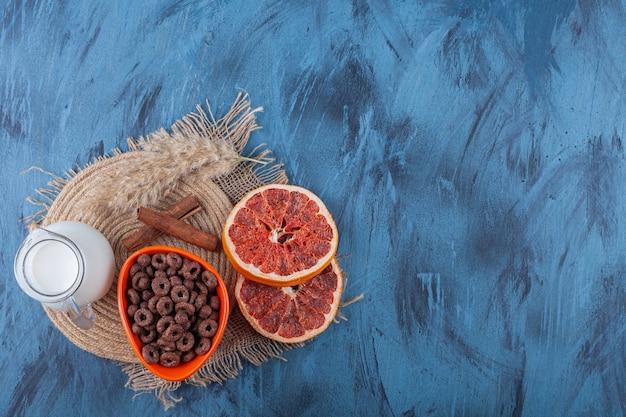 Gedroogde grapefruit, een kom met maisringen en een kan melk op een handdoek, op het blauw.