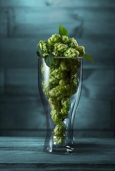 Gedroogde groene hop in een glas op de blauwe houten achtergrond