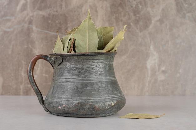Gedroogde groene laurierblaadjes in een etnische pot.
