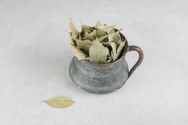 Gedroogde groene laurierblaadjes in een metalen pot.