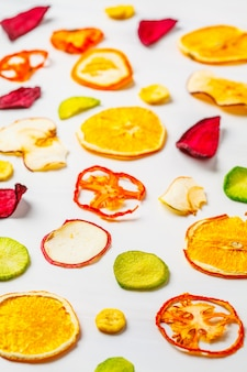 Gedroogde groenten en fruit op een witte achtergrond.