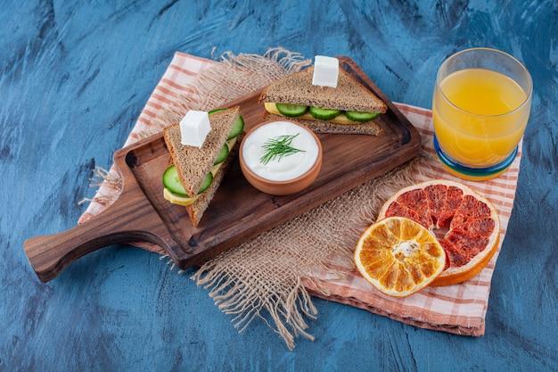 Gedroogde groenten naast een glas sap, sandwich, op een bord op jute servet, op het blauw.