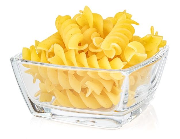 Gedroogde italiaanse pasta spiraalvormige fusilli in een kleine transparante glazen vierkante kom geïsoleerd op een witte achtergrond