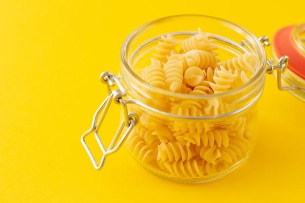 Gedroogde italiaanse pasta spiraalvormige fusilli in een open glazen pot op gele achtergrond