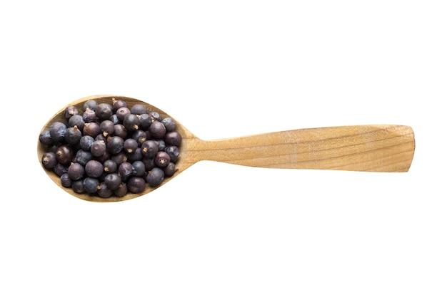 Gedroogde jeneverbessen om toe te voegen aan voedselkruiden in een houten lepel