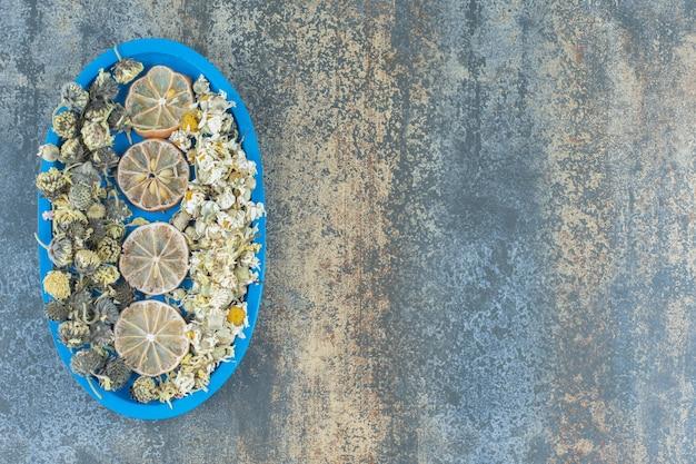 Gedroogde kamille bloemen en citroenen op blauw bord.