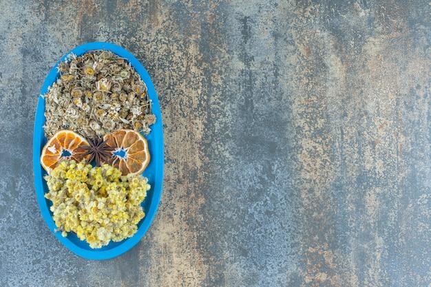 Gedroogde kamille en chrysant op blauw bord.