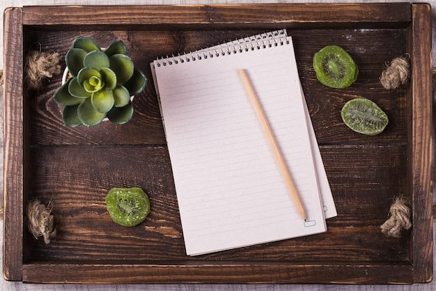 Gedroogde kiwi en een notitieblok op een dienblad